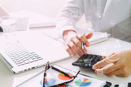 Businessman hand working with finances about cost and calculator and laptop with mobile phone on withe desk in modern office with VR icon diagram