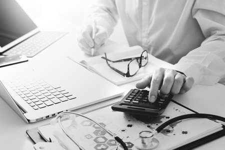 Healthcare costs and fees concept.Hand of smart doctor used a calculator for medical costs in modern hospital,black and white Banque d'images