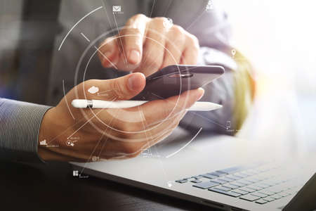 Close up of businessman working with mobile phone and stylus pen and laptop computer on wooden desk in modern office with virtual icon diagram Banque d'images