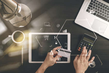 Internet shopping concept.Top view of hands working with laptop and credit card and tablet computer on dark wooden table background with Vr diagram