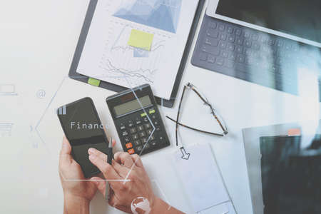 Top view of businessman hand working with finances about cost and calculator and laptop with mobile phone on withe desk in modern office with VR icon diagram