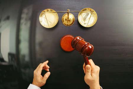Justicia y concepto de la ley. Vista superior de la mano del juez masculino en una sala de tribunal con la escala del martillo y del latón en la tabla de madera oscura Foto de archivo - 83658345
