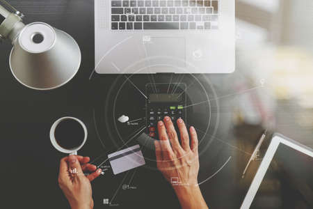 Internet shopping concept.Top view of hands working with calculator and laptop and credit card and tablet computer on dark wooden table background with Vr diagram
