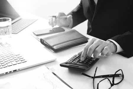 Zakenmanhand die met financiën over kosten en calculator en laptop met mobiele telefoon aan withe met bureau in modern zwart-wit bureau werken,