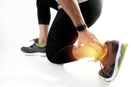 Runner sportsman holding ankle in pain with Broken twisted joint running sport injury and Athletic man touching foot due to sprain on white background Stock Photo