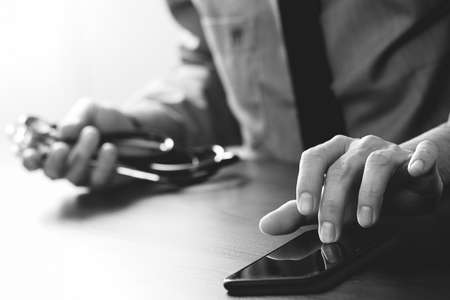 insurer: Close up of smart medical doctor working with mobile phone and stethoscope on dark wooden desk,black and white