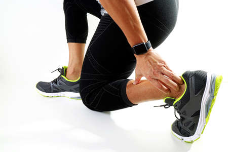 rupture: Runner sportsman holding ankle in pain with Broken twisted joint running sport injury and Athletic man touching foot due to sprain on white background Stock Photo