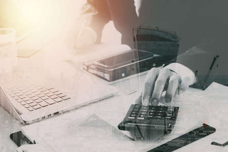 Businessman hand working with finances about cost and calculator and laptop with mobile phone on withe desk in modern office with city exposure Banque d'images