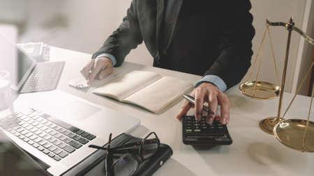 Justicia y la ley concept.businessman o abogado o contador de trabajo en las cuentas con una calculadora y ordenador portátil y documentos en la oficina moderna Foto de archivo - 83658784