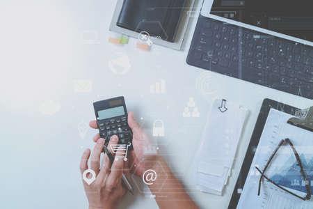 Bovenaanzicht van zakenman hand werken met financiën over kosten en rekenmachine en laptop met mobiele telefoon met bureau in modern kantoor met VR pictogram diagram