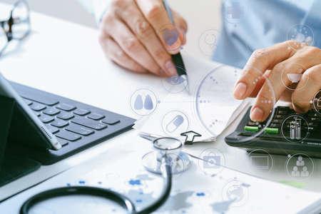 ヘルスケアの費用および費用の概念。スマート ドクターの手が VR アイコン ダイアグラムと近代的な病院での医療費のため電卓を使用