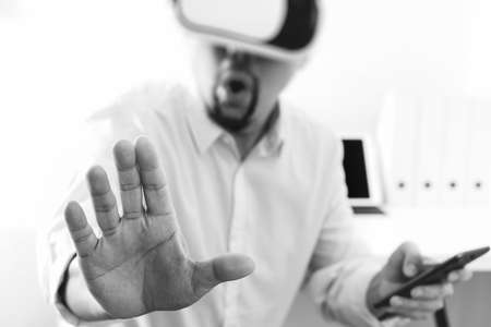 Businessman wearing virtual reality goggles in modern office with mobile phone using with VR headset,black and white Banque d'images