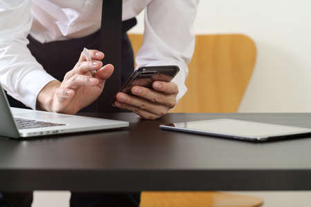 Close up of businessman working with smart phone and digital tablet and laptop computer on wooden desk in modern office