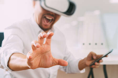 Businessman wearing virtual reality goggles in modern office with mobile phone using with VR headset Stock Photo