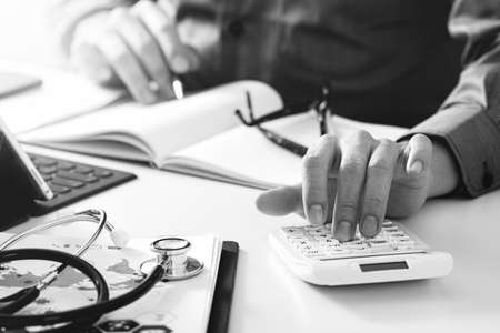 Healthcare costs and fees concept.Hand of smart doctor used a calculator for medical costs in modern hospital,black and white Stock Photo