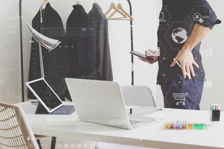 Fashion designer talking mobile phone and using laptop with digital tablet computer in modern studio with VR icon diagram