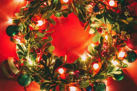 Greeting Season concept.Christmas wreath with decorative light on red background Stock Photo