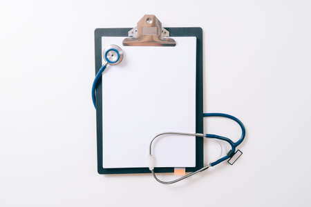 blank stethoscope and gray clipboard on white desk background Stockfoto