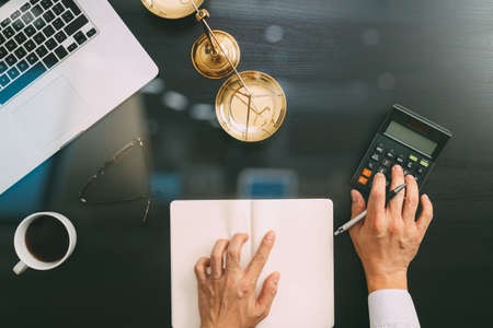 justice and law concept.businessman or lawyer or accountant working on accounts using a calculator and laptop computer and documents in modern office