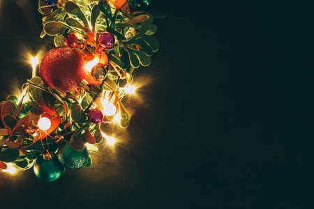 Greeting Season concept.Christmas wreath with decorative light on dark wood background Stock Photo