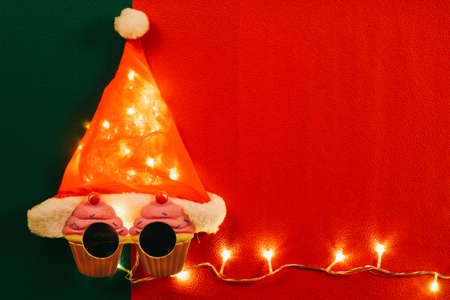 christmas gift: Greeting Season concept.Santa Claus hat with star light and glasses that decoration with Christmas cupcake on red and green background