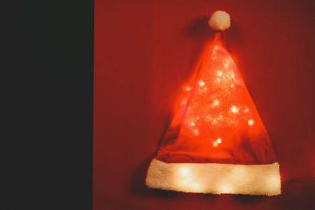 christmas gift: Greeting Season concept.Santa Claus hat with christmas light on red and green background Stock Photo