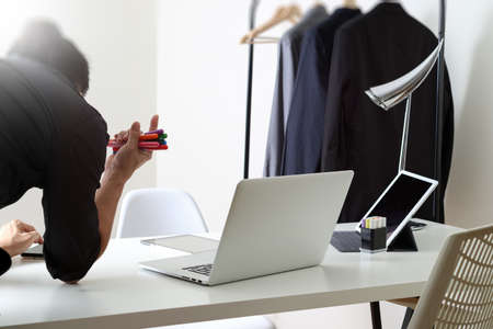 Fashion designer working with mobile phone and using laptop with digital tablet computer in modern studio with city exposure