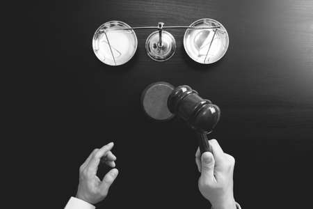 justice and law concept.Top view of Male judge hand in a courtroom with the gavel and brass scale on dark wood table,black and white