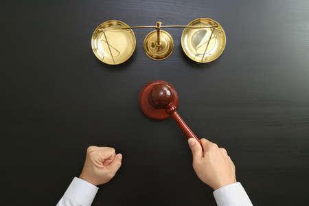 Concetto di giustizia e di legge.Top vista della mano maschio giudice in una sala di tribunale con la scala di ottone e ottone sul tavolo di legno scuro Archivio Fotografico - 85987439