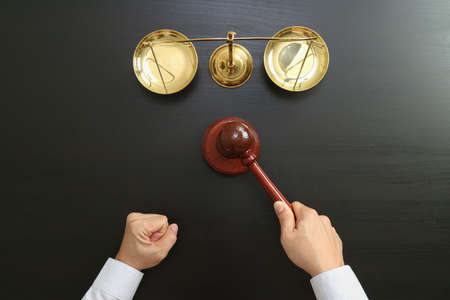 La justicia y el concepto de la ley. Vista superior de la mano del juez masculino en una sala de tribunal con el martillo y la escala de latón en la mesa de madera oscura Foto de archivo - 85987439