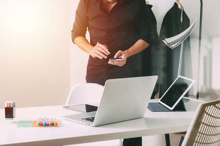 Fashion designer working with mobile phone and using laptop with digital tablet computer in modern studio
