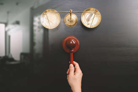 Concetto di giustizia e di legge.Top vista della mano maschio giudice in una sala di tribunale con la scala di ottone e ottone sul tavolo di legno scuro Archivio Fotografico - 85987500