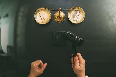 Le concept de la justice et de la loi.La vue du juge masculin maintient une salle d'audience avec le marteau et l'échelle en laiton sur la table en bois sombre Banque d'images - 88995767