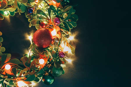 Greeting Season concept.Christmas wreath with decorative light on dark wood background Zdjęcie Seryjne