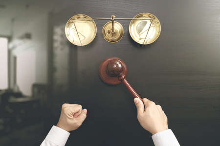 justice and law concept.Top view of Male judge hand in a courtroom with the gavel and brass scale on dark wood table