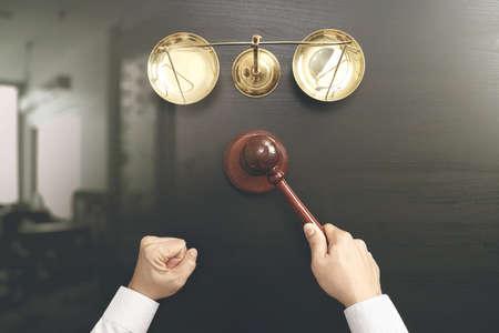 Le concept de la justice et de la loi.La vue du juge masculin maintient une salle d'audience avec le marteau et l'échelle en laiton sur la table en bois sombre Banque d'images - 88996379