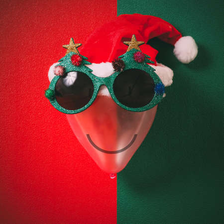 Christmas glasses that decoration with Christmas tree and red hat on air bolloon   on green background