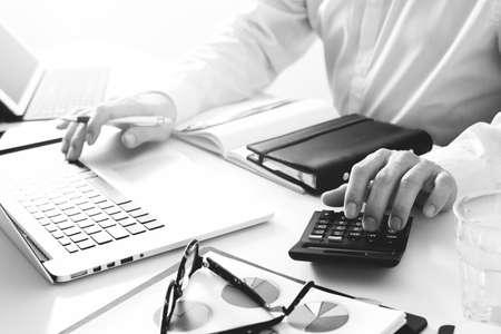 zakenman hand werken met financiën over kosten en rekenmachine en latop met mobiele telefoon op met bureau in moderne kantoor, zwart en wit