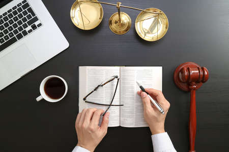 justice and law concept.Top view of Male judge hand in a courtroom with the gavel and brass scale and computer and open bible book on dark wood table Stock Photo