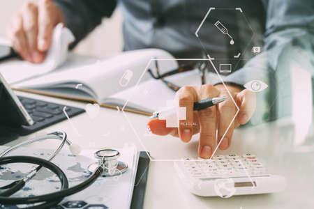 Gezondheidszorg kosten en kosten concept.Hand van slimme arts gebruikte een rekenmachine voor medische kosten in het moderne ziekenhuis met VR pictogram diagram