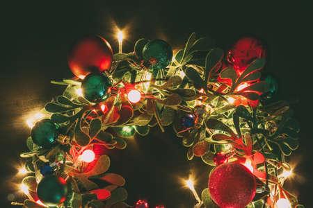 Gruß-Saison-Konzept.Christmas Kranz mit dekorativen Licht auf dunklen Holz Hintergrund Standard-Bild