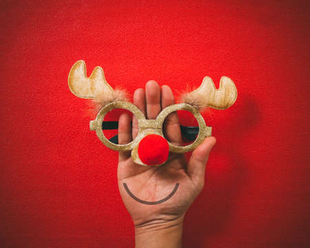 Christmas glasses that decoration with Christmas reindeer and red ball on hand on red  background