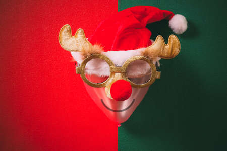 Christmas glasses that decoration with reindeer and red hat on air bolloon on green and red background