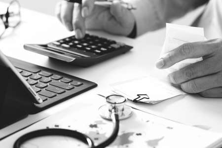 Healthcare costs and fees concept.Hand of smart doctor used a calculator for medical costs in modern hospital,black and white Standard-Bild
