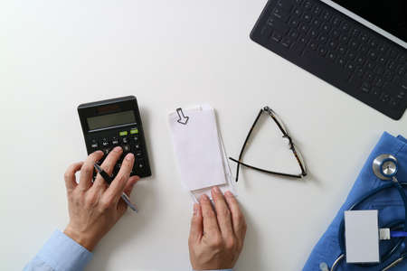 top view of Healthcare costs and fees concept.Hand of smart doctor used a calculator for medical costs in modern hospital