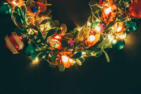 Greeting Season concept.Christmas wreath with decorative light on dark wood background Standard-Bild