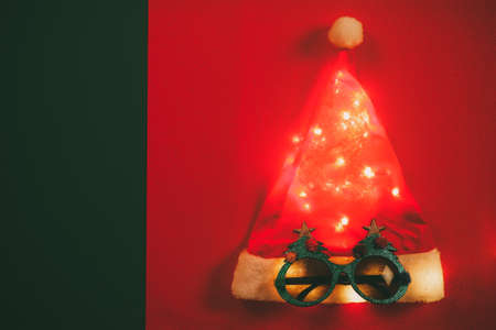 Greeting Season concept.Santa Claus hat with star light and glasses that decoration with Christmas tree on red and green background