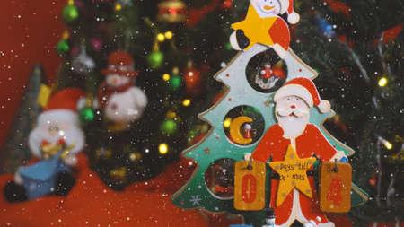 Gruß-Jahreszeitkonzept. Santa Claus-Show 4 Tage bis Weihnachten mit Verzierungen auf einem Weihnachtsbaum mit dekorativem Licht
