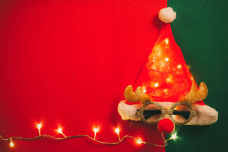 Greeting Season concept.Santa Claus hat with star light and glasses that decoration with Christmas reindeer on red and green background