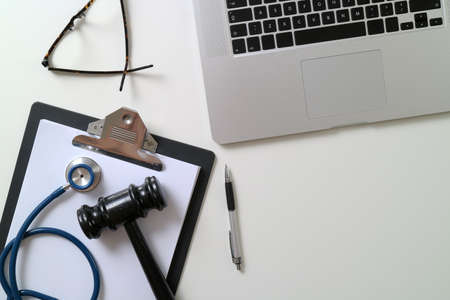 Dark Gavel With Medical Stethoscope near Laptop on white desk In Courtroom concept